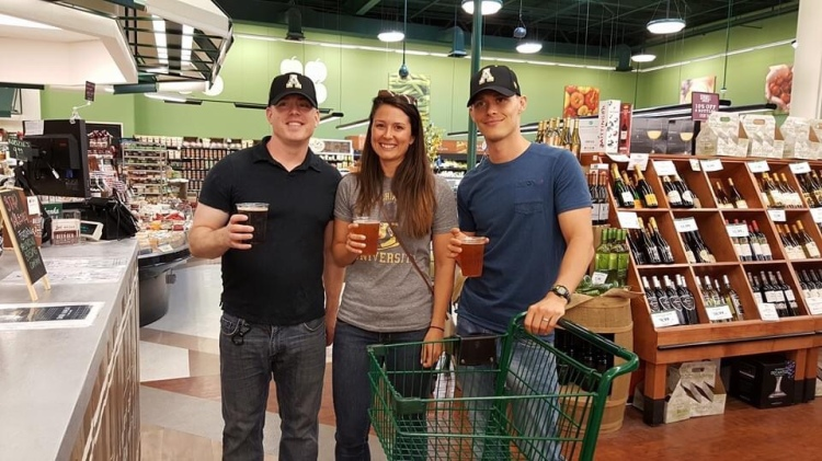 In the grocery store with a beer.