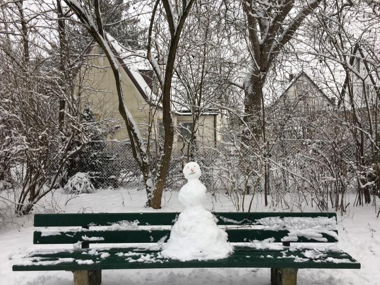 A snowman on a bench.
